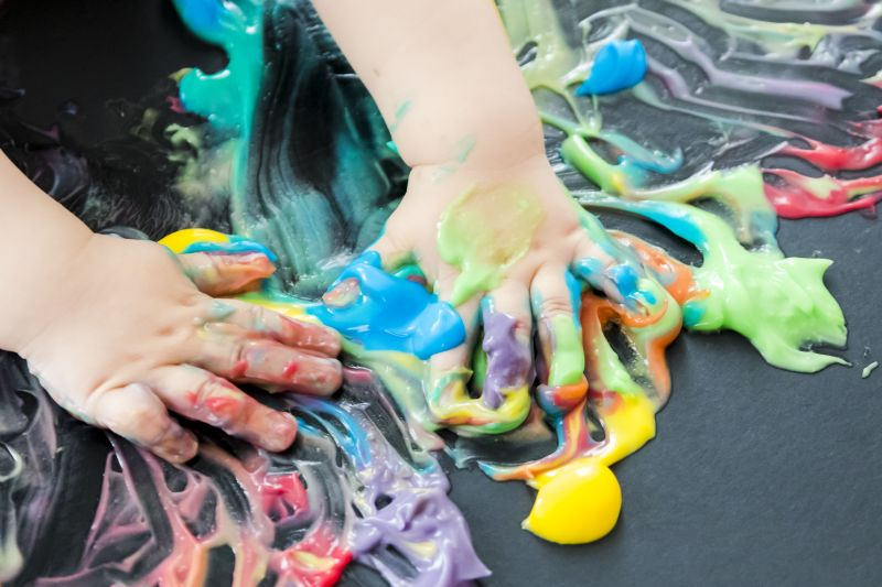 baby painting with colored paint with his hands