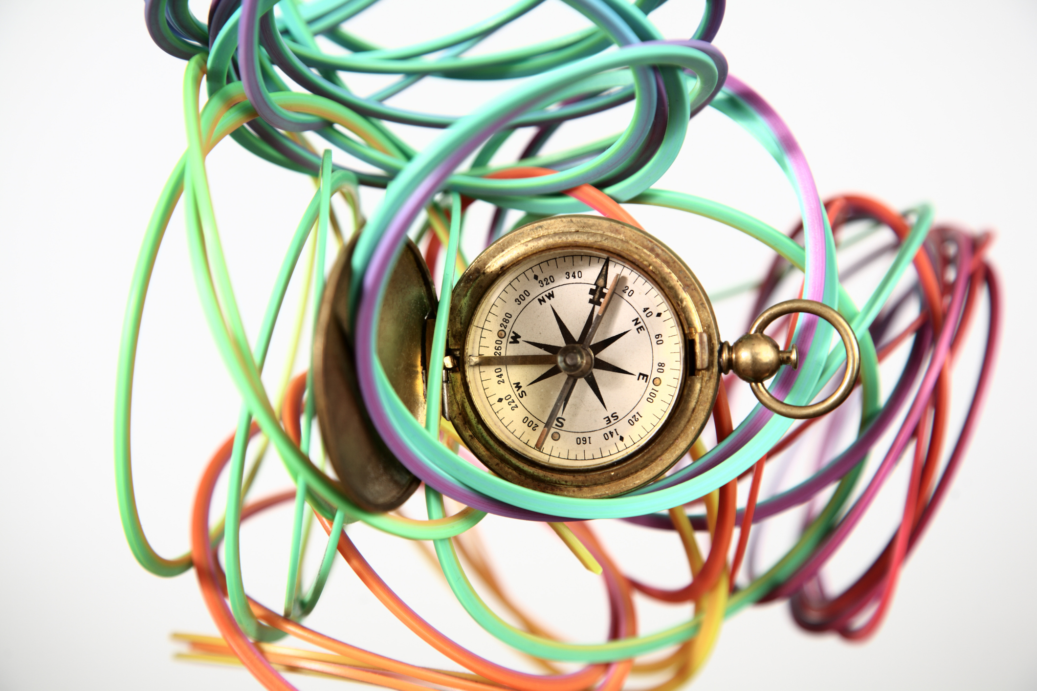 Vintage brass pocket compass in a colorful circular tangled plastic strand.
